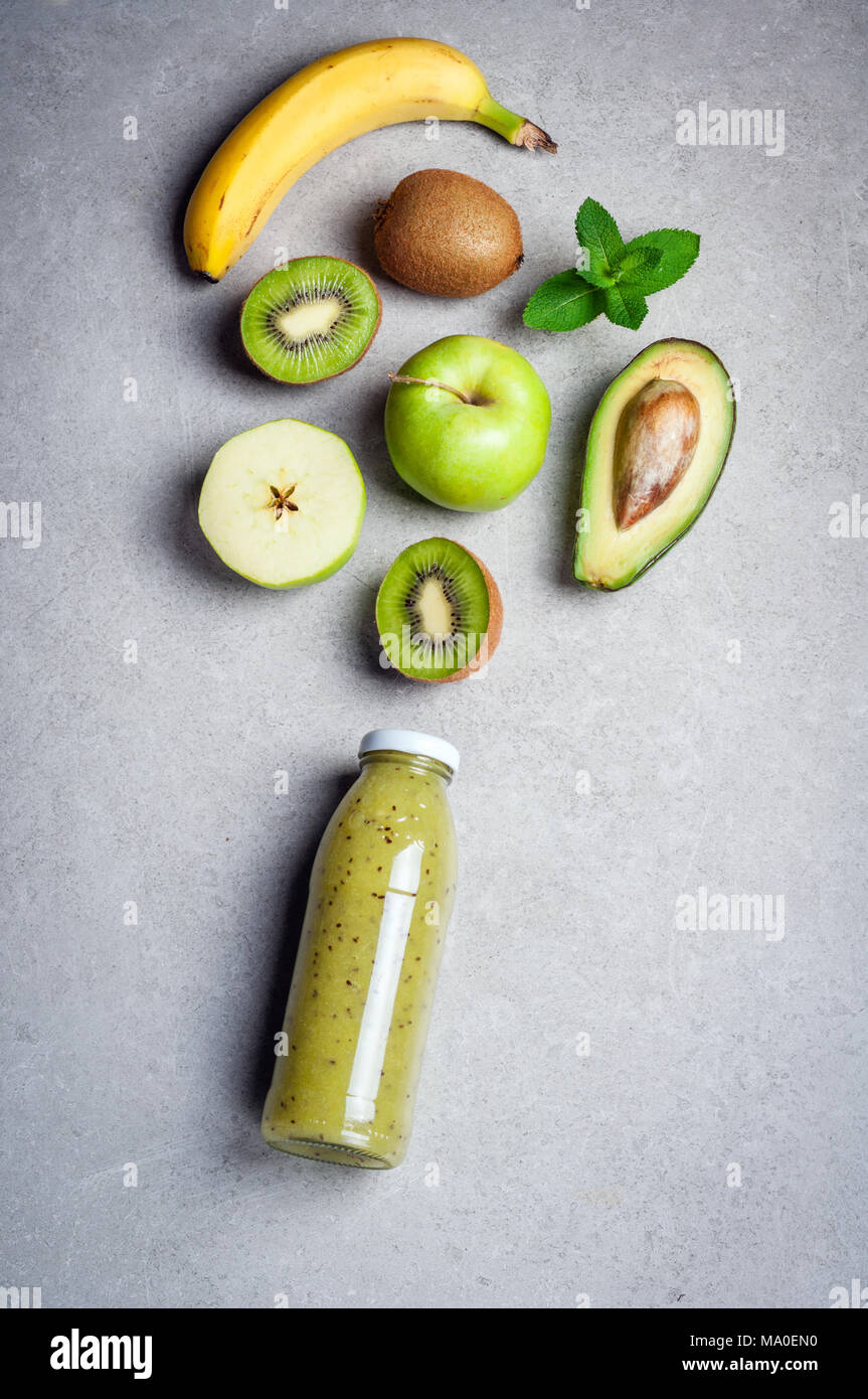 Healthy green smoothie and ingredients on grey background. Kiwi smoothie with fruits banana, avocado and apples. Superfoods, diet, detox, health, vege Stock Photo