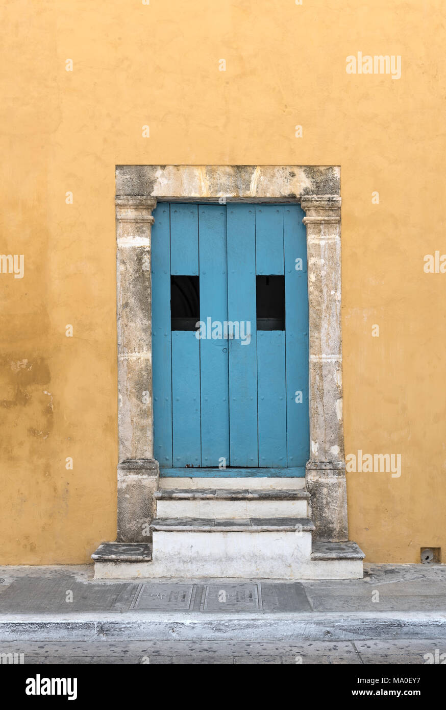 Yellow house with blue wooden door in San Francisco de Campeche, Mexico - Stock Image