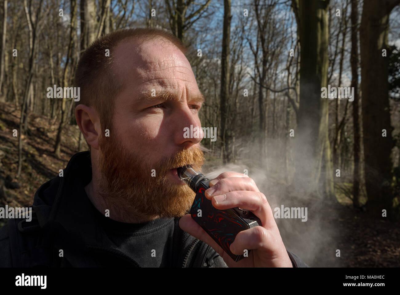 A ginger bearded man vapes on a box mod with glass vaporiser. - Stock Image