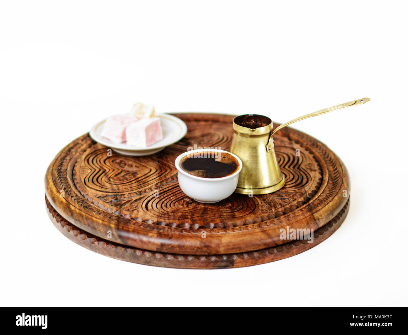 Turkish coffee served  in a traditional manner in a fildzan. It was made in the brass cezve, served with a few cubes of rahat lokum as a sweet snack. - Stock Image