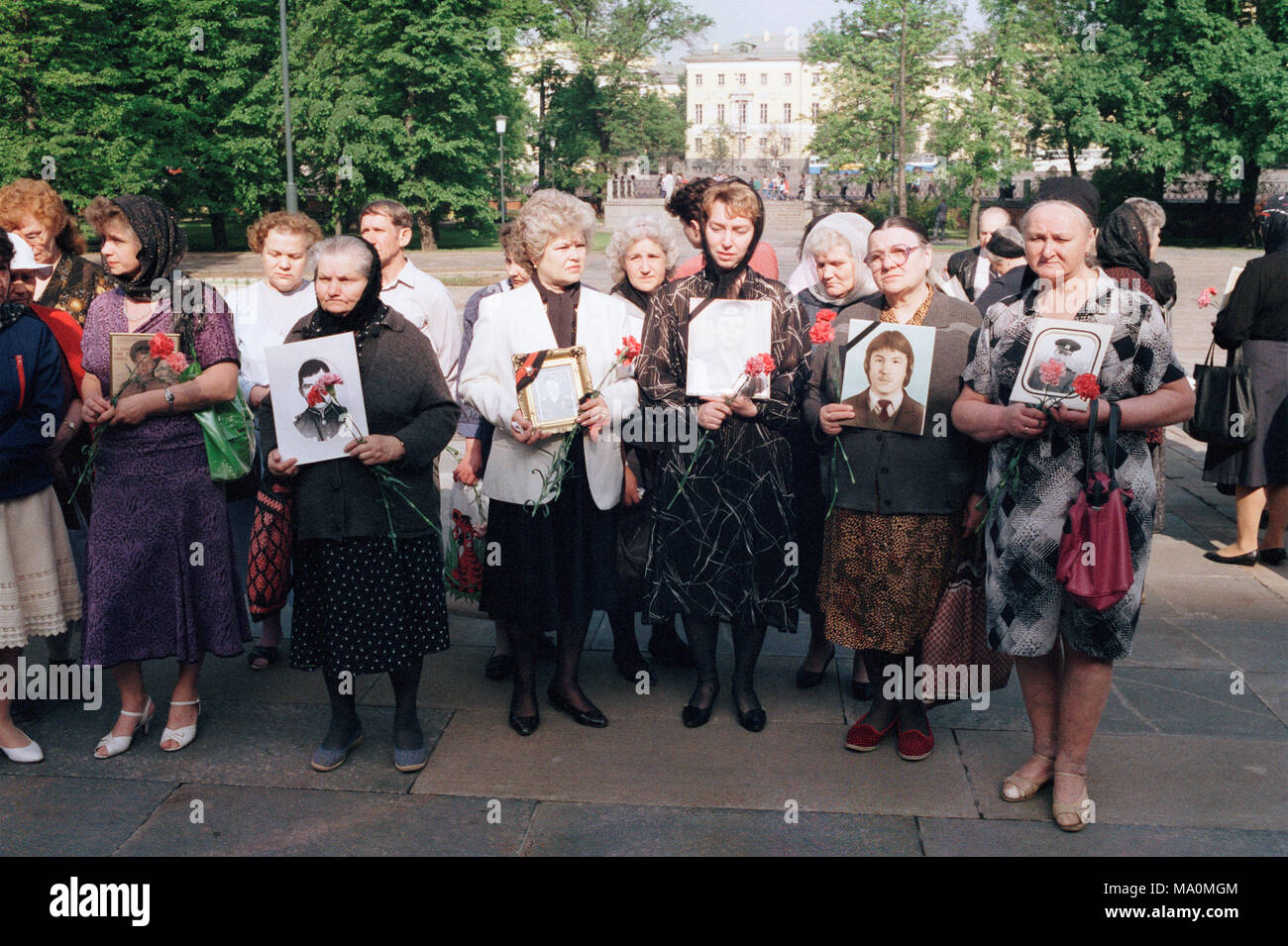 Moscow, Russia - July 10, 1992: Remembrance day of dead russian soldiers organised by Committee of Soldiers' Mothers of Russia. Mothers holding portraits of their perished sons and flowers to lay them on the tomb of unknown soldier. - Stock Image