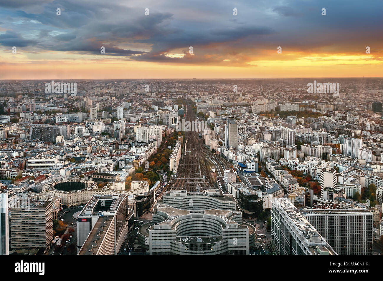 Overview of Paris from Montparnasse Tower with Montparnasse train station in the foreground. France in autumn sunset. - Stock Image