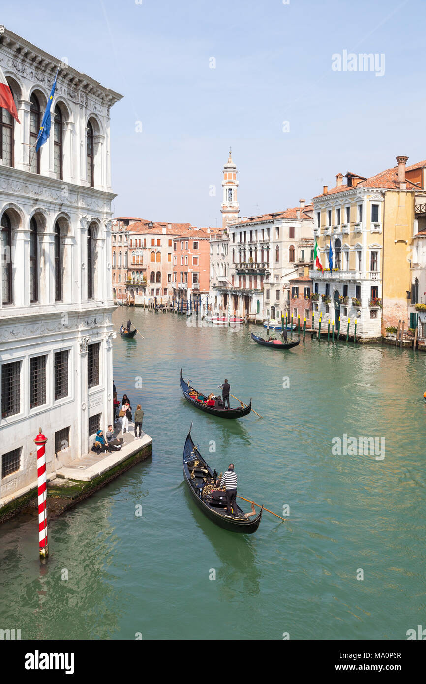 Elevated view of gondolas on the Grand Canal, San Polo, Venice, Veneto, Italy taking groups of tourists on a sightseeing tour - Stock Image