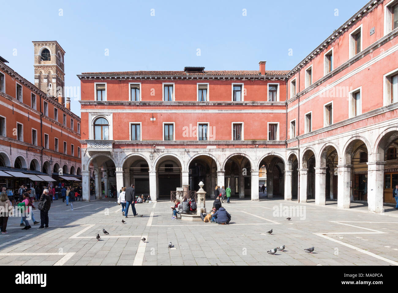 Campo San Giacomo di Rialto, Rialto, San Polo, Venice, Veneto, Italy with the statue of Il Gobbo di Rialto at the back  and people enjoying the spring - Stock Image
