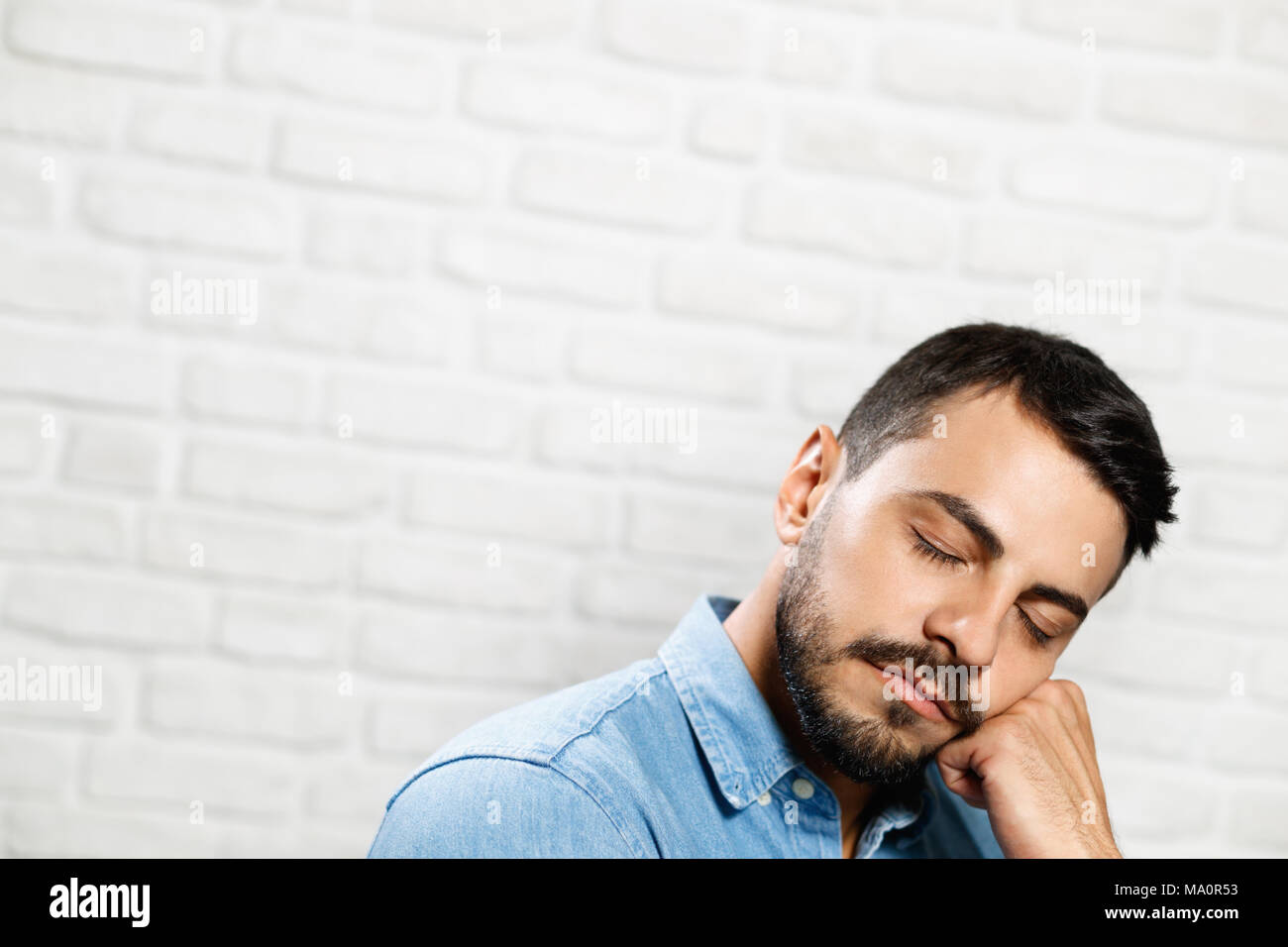 Portrait of man looking at camera. Tired Italian man yawning and doing hand gestures for concept of sleeping. - Stock Image
