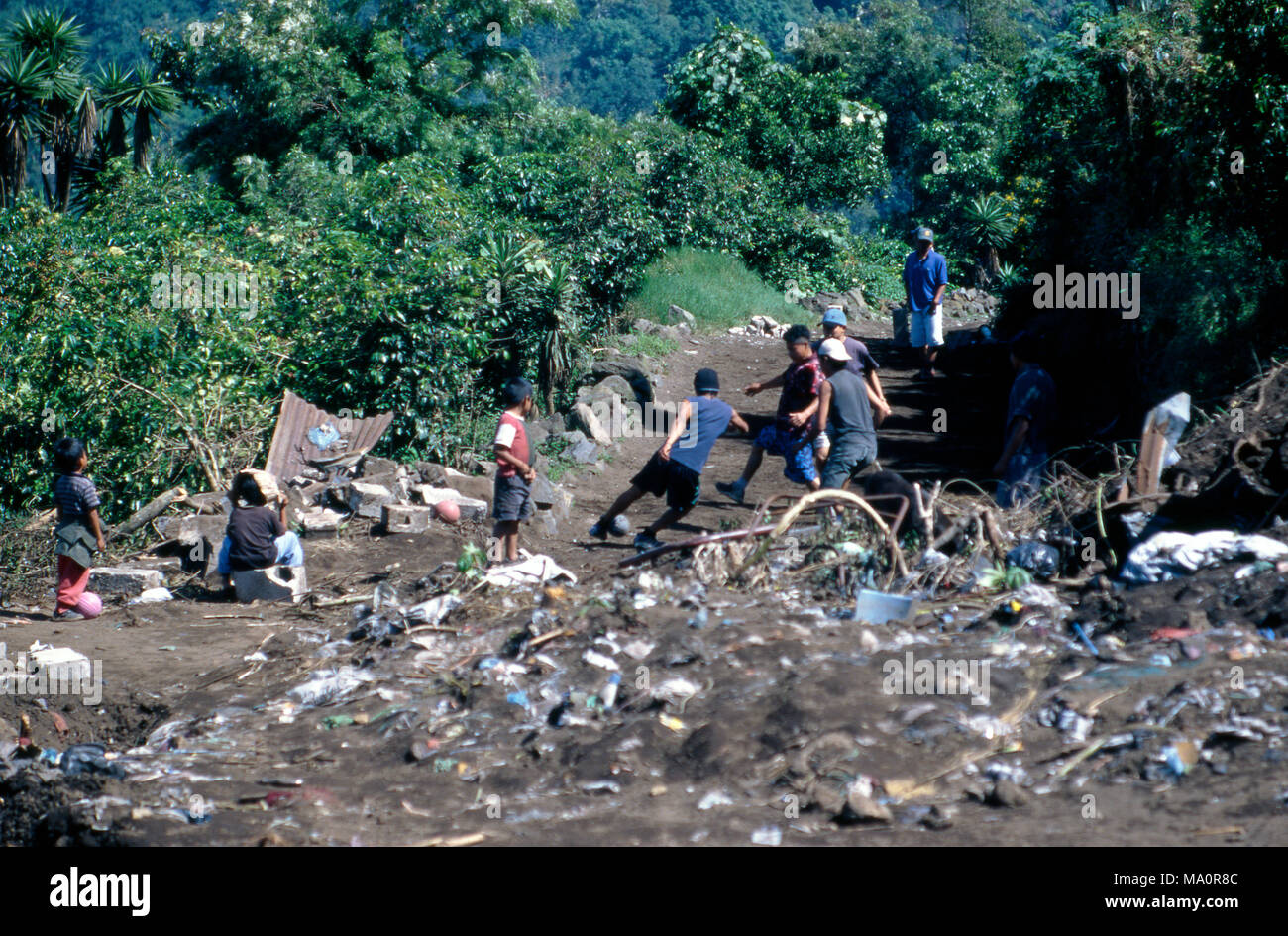Indigenous Tz'utujil Mayan boys playing football (soccer) at a rubbish dump (garbage heap) in San Lucas Tolimán, Guatemala. - Stock Image