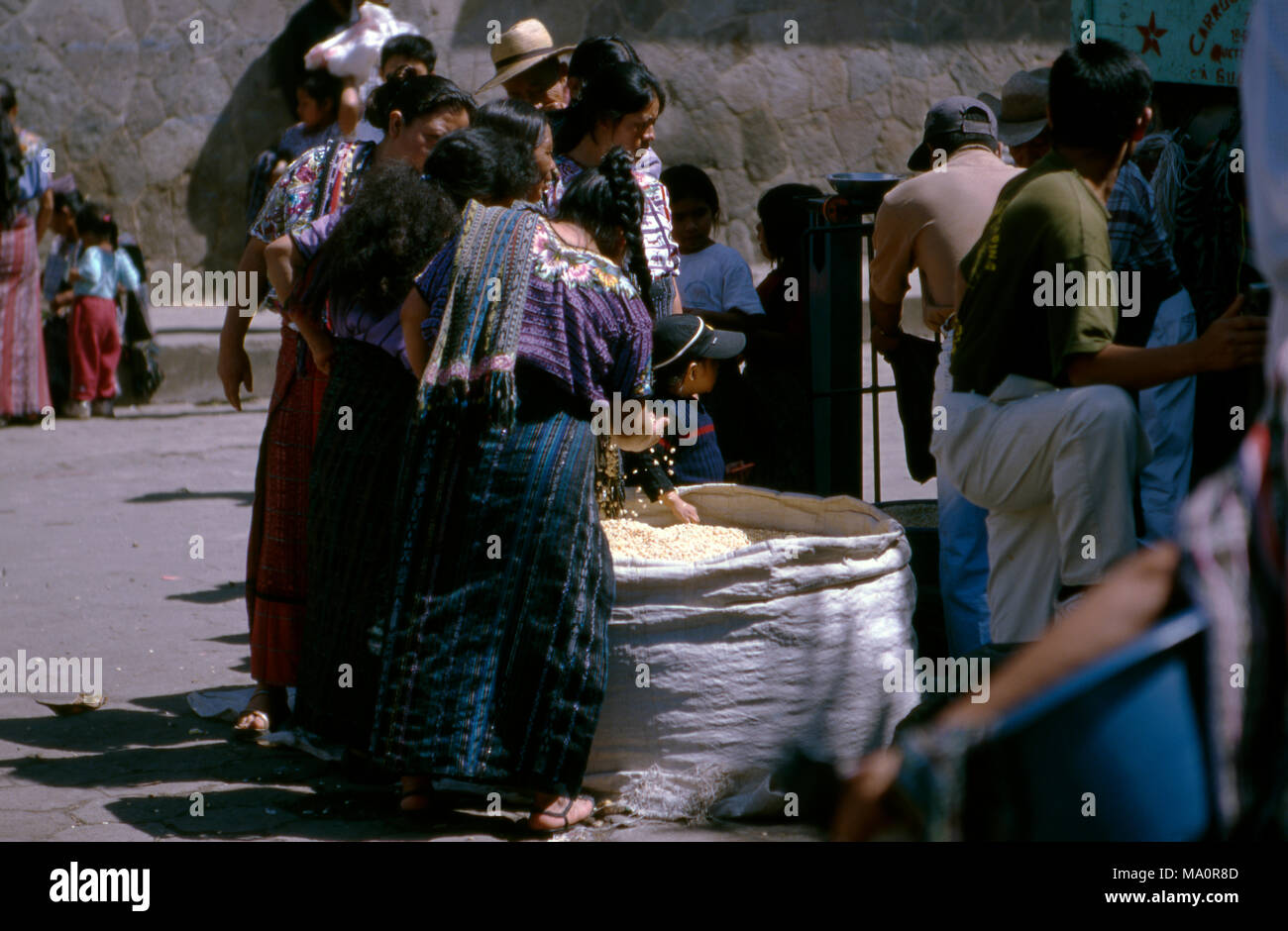 Indigenous Tz'utujil Mayan women buying corn (maize) at the market in San Lucas Tolimán, Guatemala. - Stock Image