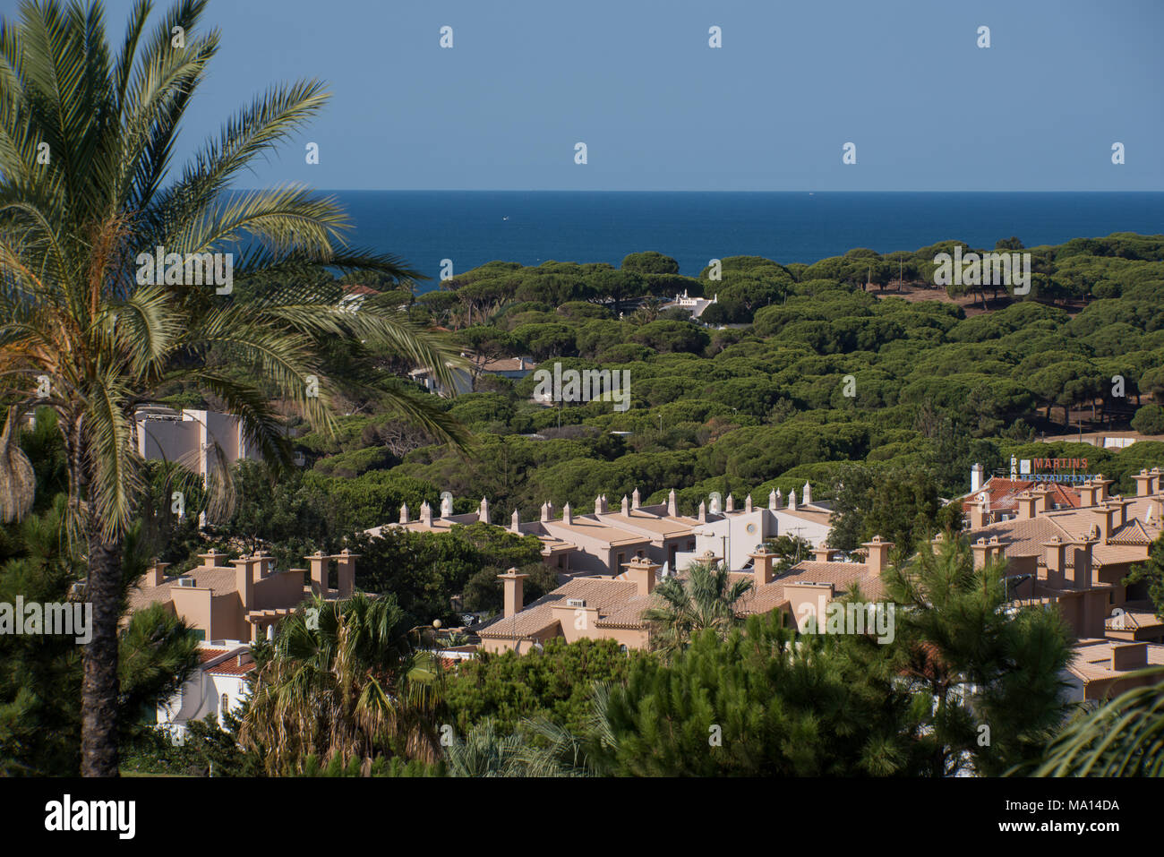 View over the Atlantic Ocean and wooded coastal development near Albufeira, Portugal - Stock Image