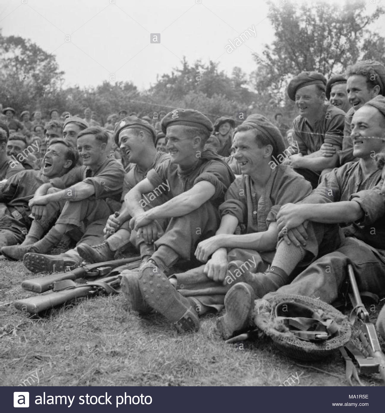 War Office Second World War Official Collection After his meal and his bath Parkhouse goes with the other members of his section to a concert by the divisional concert party. Here he is (centre), with his colleagues, enjoying one of the comedians jokes - Stock Image