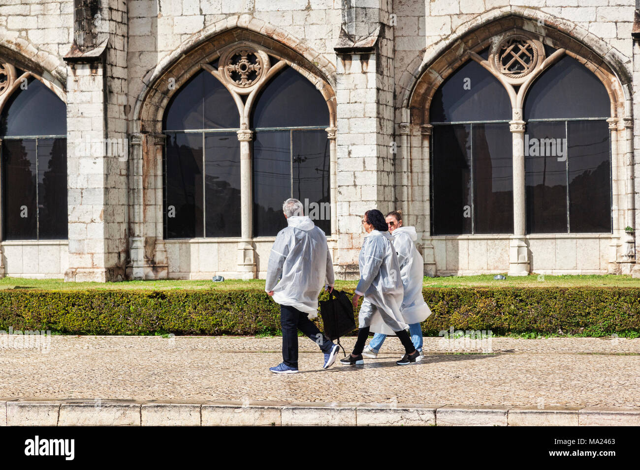 5 March 2018: Lisbon, Portugal - Family wearing rain capes after a shower of rain at the Monastery of Jeronimos Belem Lisbon Portugal - Stock Image