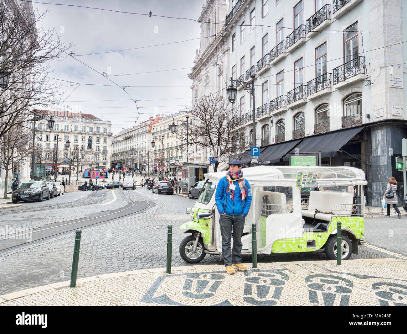 7 March 2018: Lisbon, Portugal - Tuk tuk driver wrappede up warm,  waiting for business on the streets of Lisbon in early spring. - Stock Image