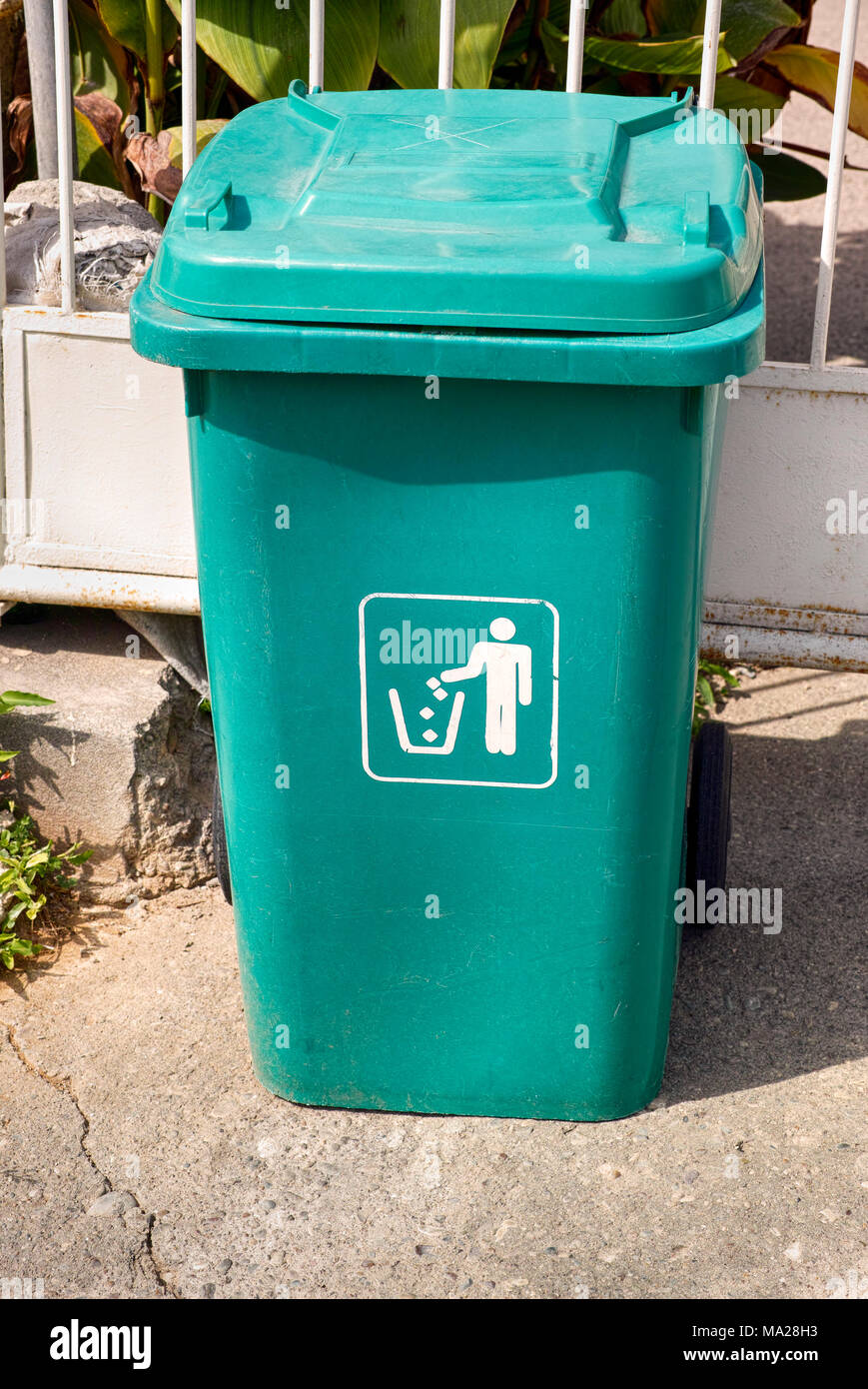Green garbage can stands in front of fence. - Stock Image