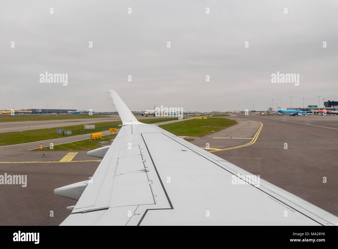 A view out of a landed passenger airplane taxiing along a runway looking at queue of lined up aircraft at Amsterdam Airport Schiphol, Netherlands. - Stock Image