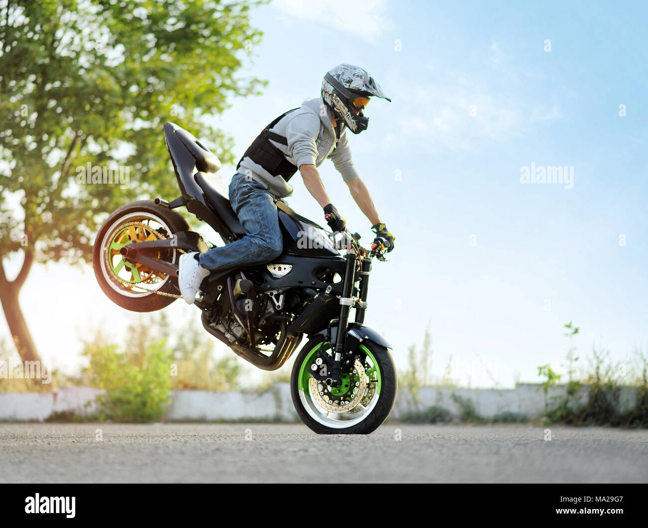 Ivano-Frankivsk, Ukraine - 28 August 2015 : Photo of biker is doing extreme trick on one cycle on blue summer sky and green trees background. Showing his talents and doing tricks wearing helmet. - Stock Image