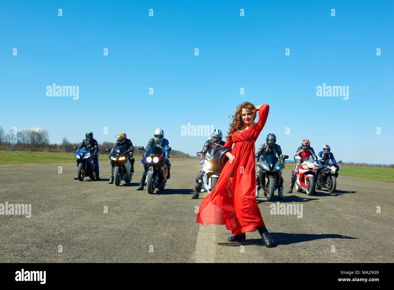 Kiev, Ukraine - 29 March 2017: Young woman in dispersing red dress is posing in front of seven bikers sitting on motorcycles somewhere on long road on green field. Emotional, colorful, original. - Stock Image