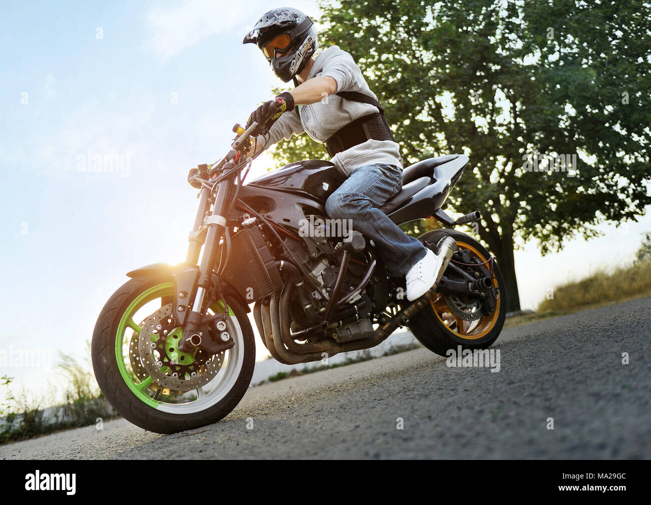 Ivano-Frankivsk, Ukraine - 28 August 2015 : Photo of biker is posing sitting on his colorful sport motorcycle on summer street, filled with shine of sunset. Man wearing protective helmet for bikers. - Stock Image