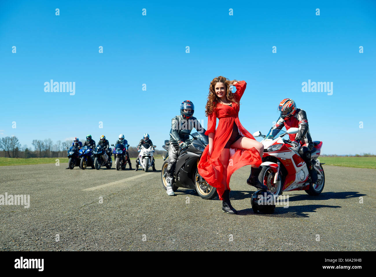 Kiev, Ukraine - 29 March 2017: Photo of young beatiful lady wearing red dispersing dress and posing in front of seven bikers, sitting on their motorcycles on blue sky background. - Stock Image