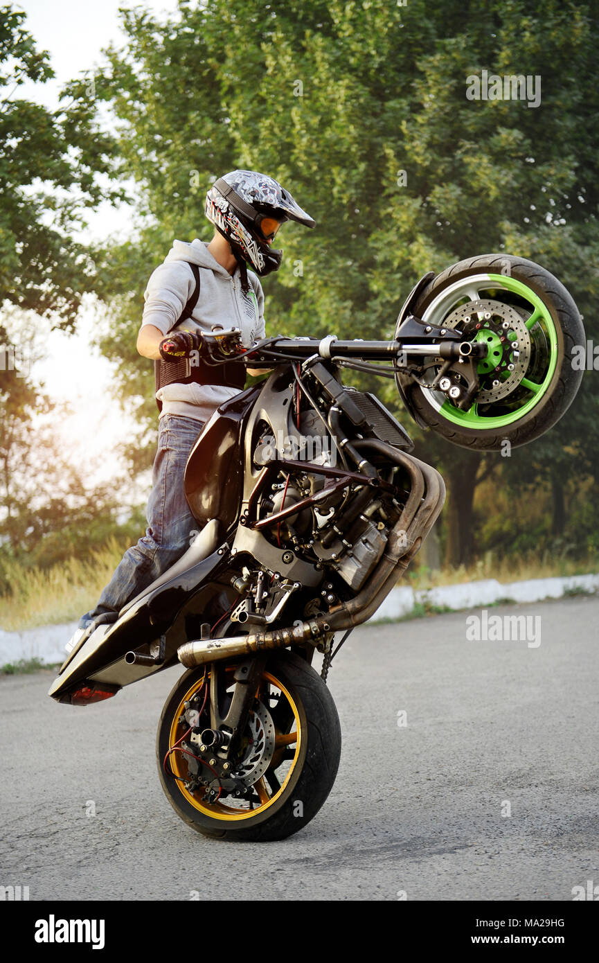 Ivano-Frankivsk, Ukraine - 28 August 2015 : Good photo of a stuntman doing trick riding motorcycle on one cycle along the street. Green tricks on background. Summer sunset. - Stock Image
