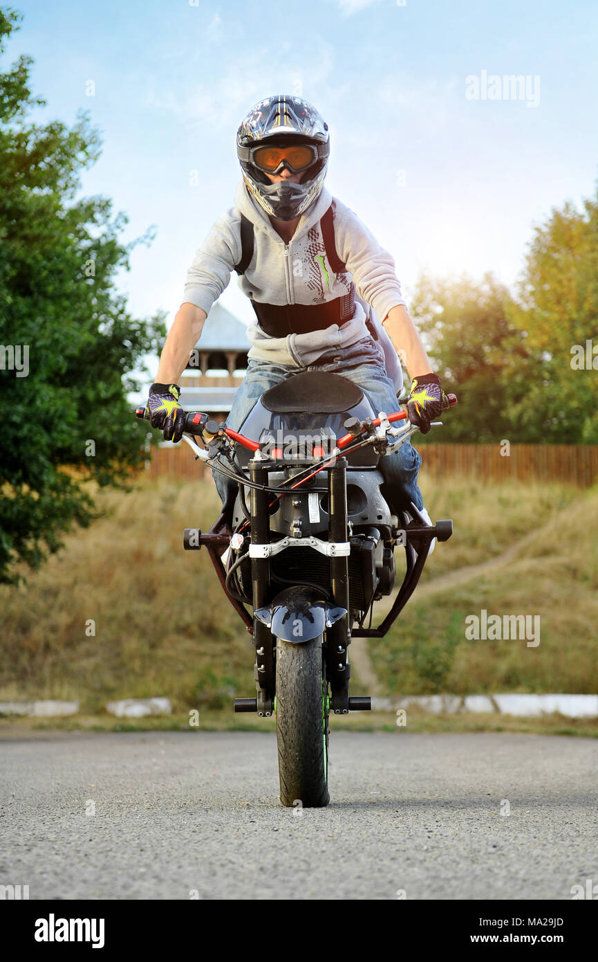 Ivano-Frankivsk, Ukraine - 28 August 2015 : Young extreme biker looking at camera sitting on sport motorcycle , wearing helmet, jeans and jacket. Blue sky and green trees on background. warm colors. Stock Photo