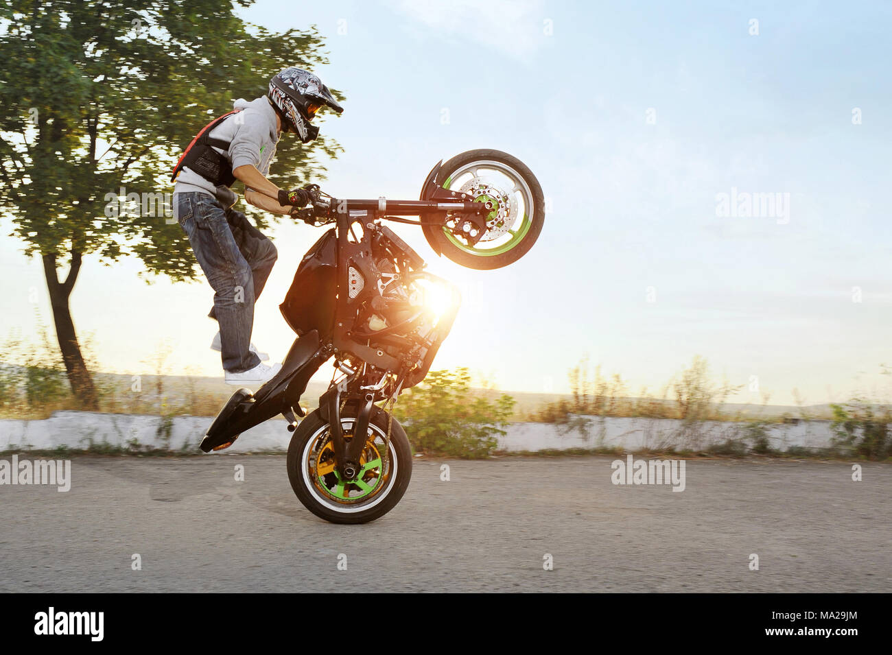 Ivano-Frankivsk, Ukraine - 28 August 2015 : colorful sideview of extreme impressing stunt driver is jumping on his sport motorcycle while riding in extreme way. Summer sunny evening. Stock Photo