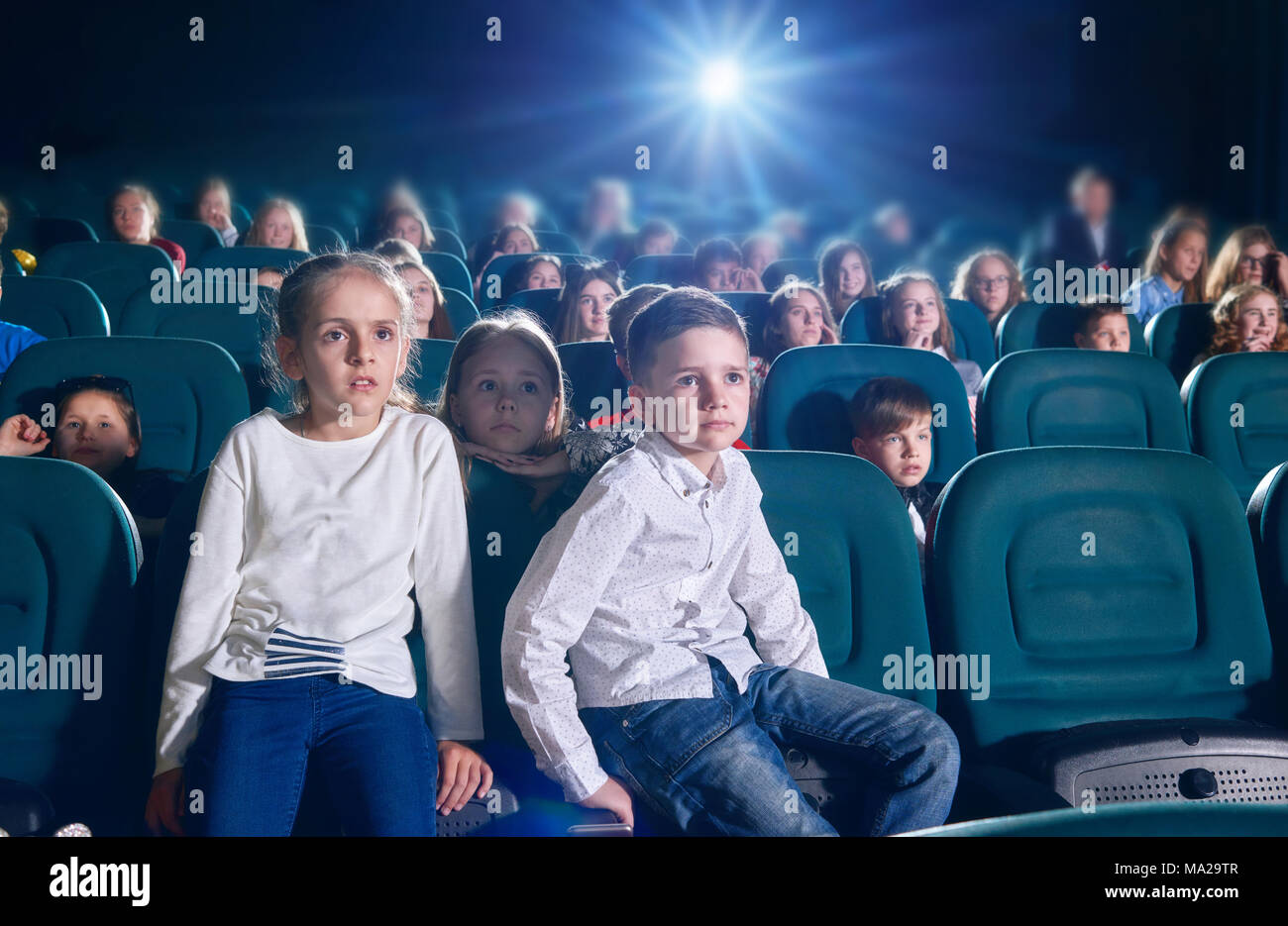 Frontview of boy and girl sitting in the cinema hall by watching new movie or cartoon. Boy is looking at camera, girl is watching film on the cinema screen. exited, emotional children on background. Stock Photo
