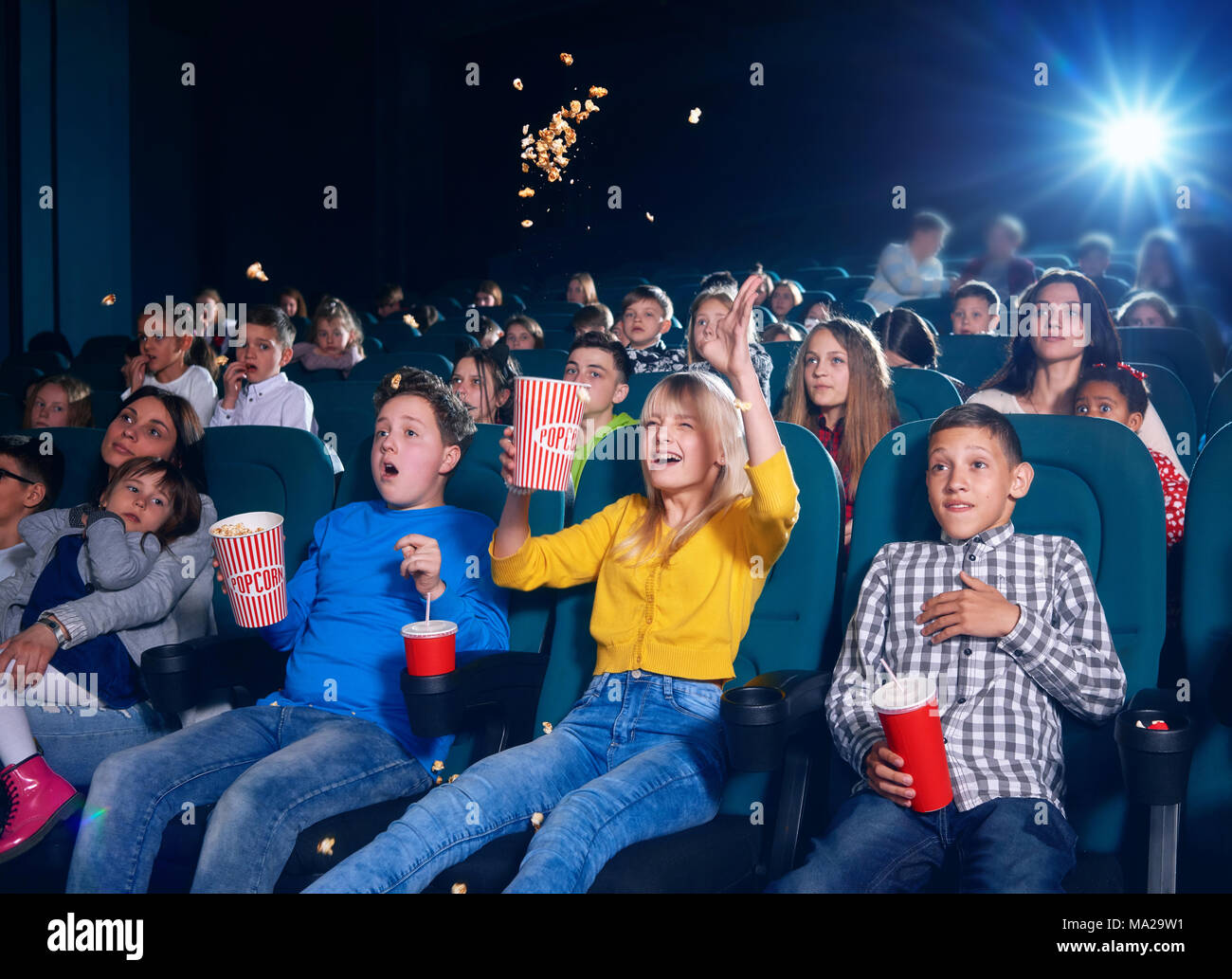 Photo of children sitting on first cinema row. Schoolmates very emotional,exited,surprised,happy and satisfied. girl wearing yellow cardigan spilling up popcorn by watching movie. - Stock Image