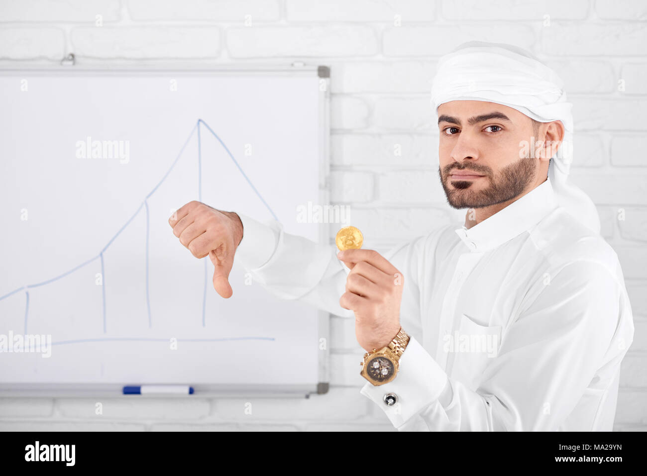 Attractive rich muslim male model in traditional Islamic clothing being serious and holding golden bitcoin and showing thumbs down. Horizontal shot. Financial problems, cryptocurrency, digital money. - Stock Image