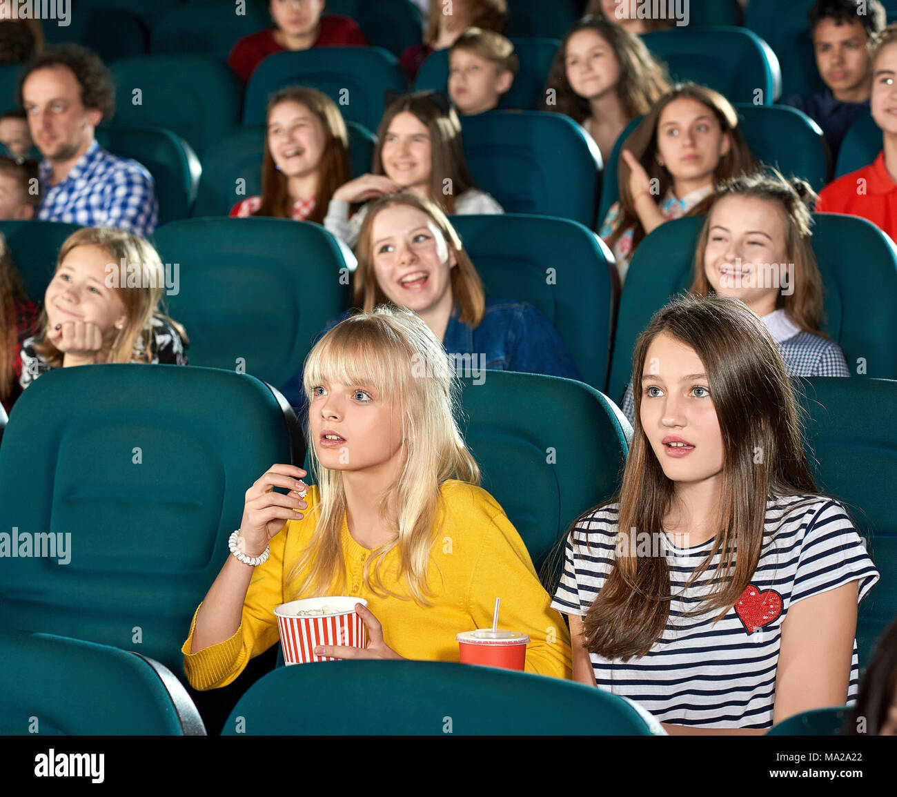 Exited girls watching movie in the cinema. Children ooking very interested, drinking fizzy drinks, sitting on other children's background. They wearing trendy colorful clothes. looking frightened. - Stock Image