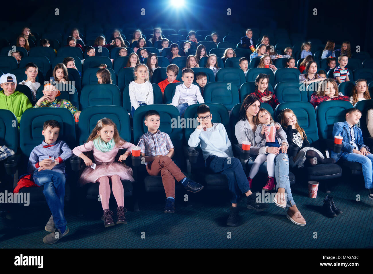 Frontview of people sitting in the cinema hall. Boys and girls watching interesting movie and looking very emotional, frightened and exited. Children wear colorful trendy clothes. - Stock Image