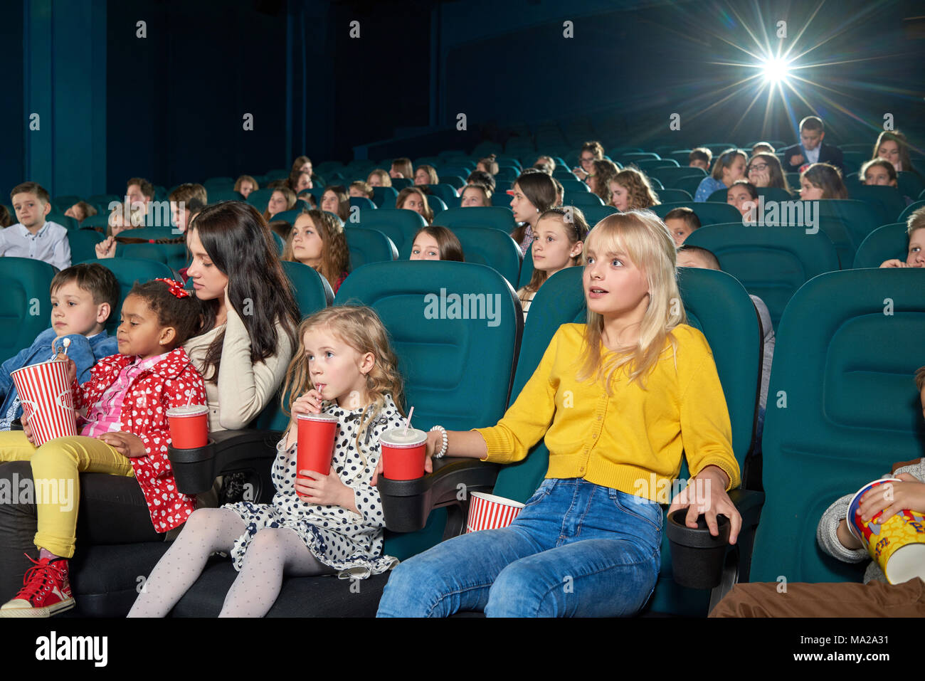 Interested girls watching new movie in the cinema. Children drinking fizzy drinks and eating popcorn. Looking emotional, exited, happy and satisfied. Other people on background. - Stock Image