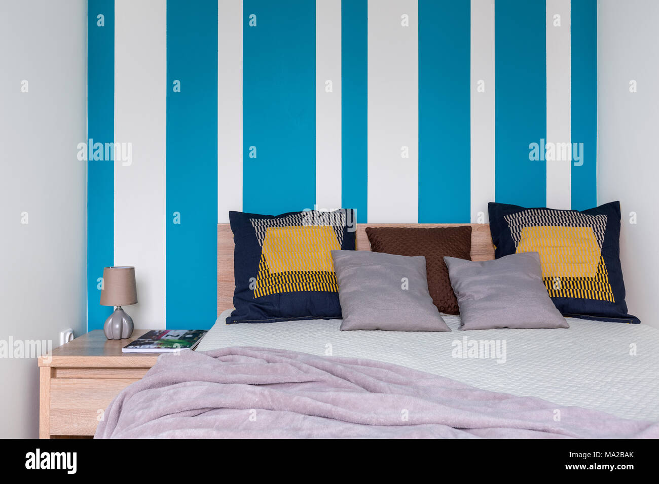 Cozy Bedroom With Big Bed Decorative Cushions And Striped Wall In White And Blue Stock Photo Alamy