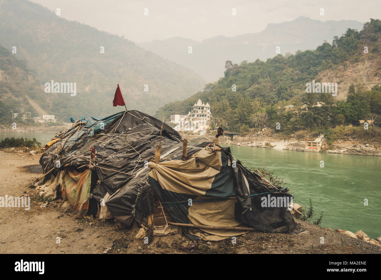 Beggar's hut by the river Ganges Rishikesh on the background of a large expensive temple. lower caste. Social inequality. The problem of poverty and t - Stock Image