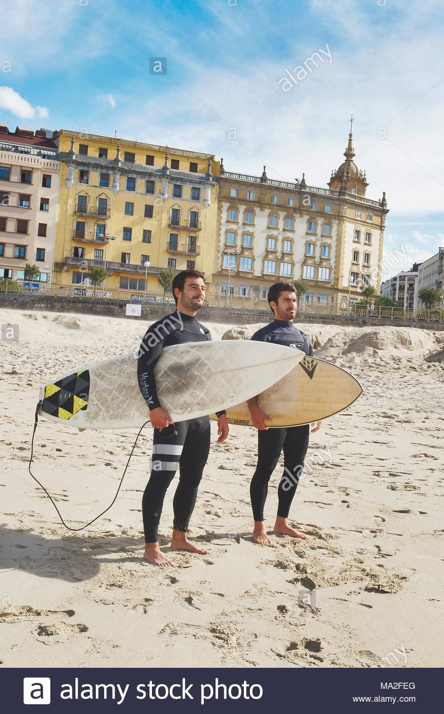 Two surfers on Zurriola beach, Spain - Stock Image