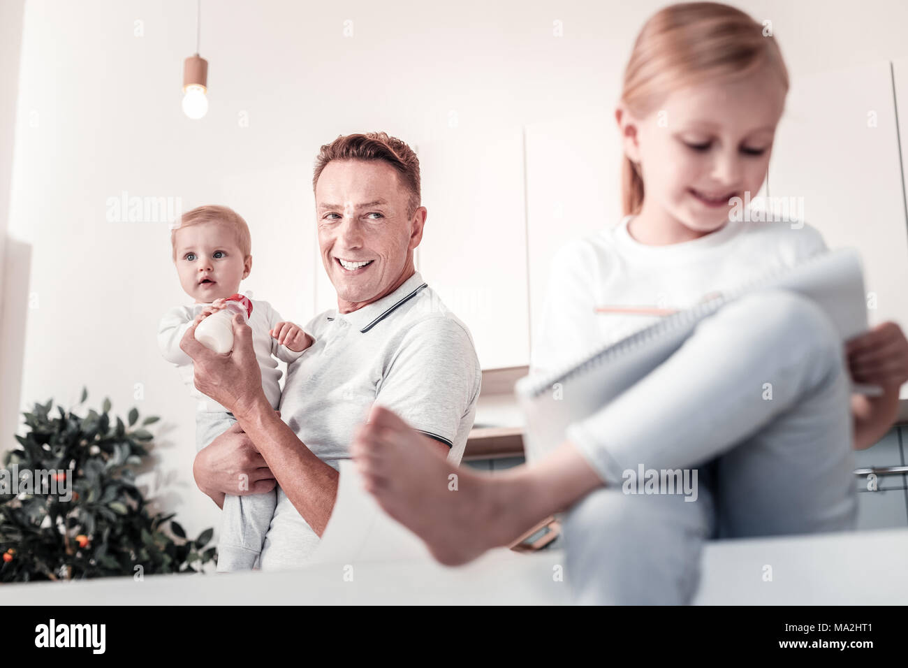 Happy male person looking at his kid - Stock Image
