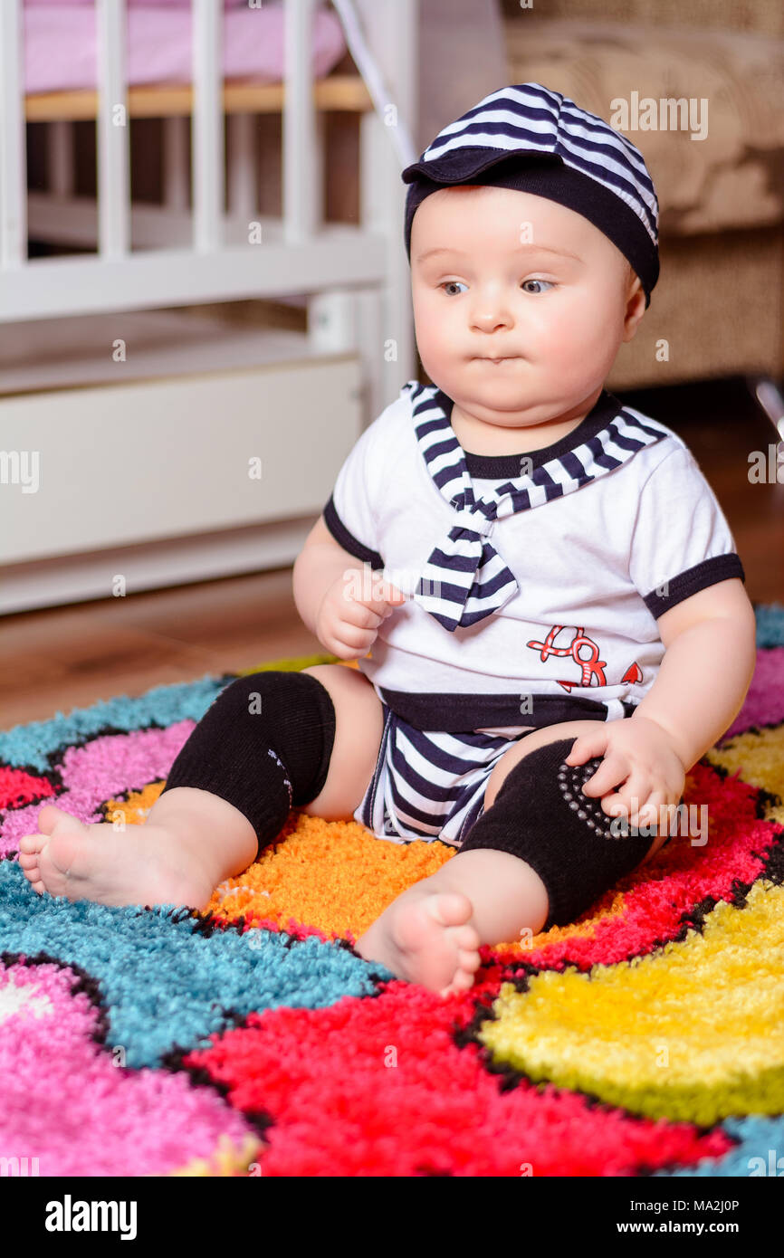 A Pretty Baby In A Striped Shirt And Hats Seated On The Mat In The