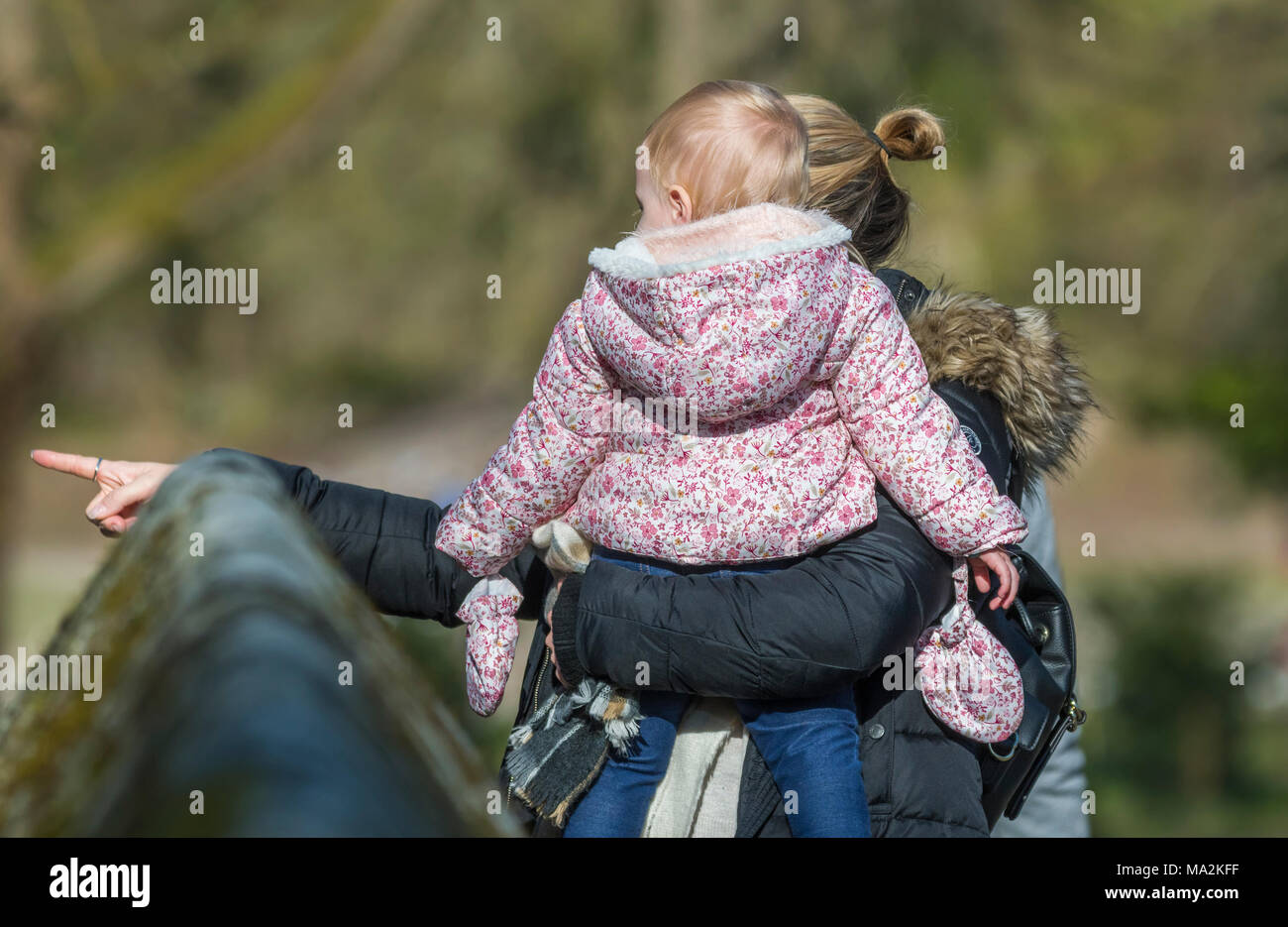 Woman carrying young baby pointing something out on a day out in the UK. - Stock Image