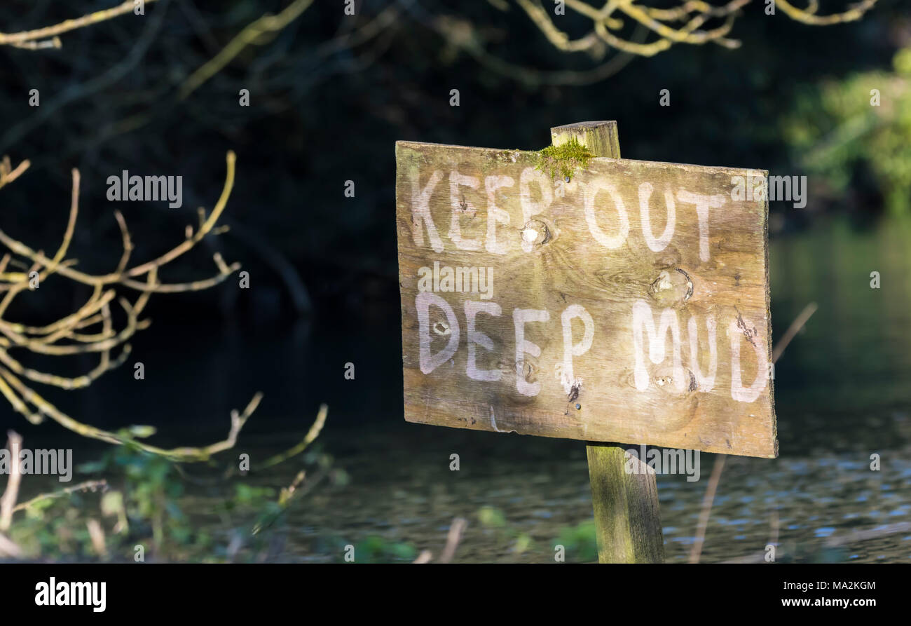 Keep out deep mud danger warning sign in a muddy lake in the UK. - Stock Image