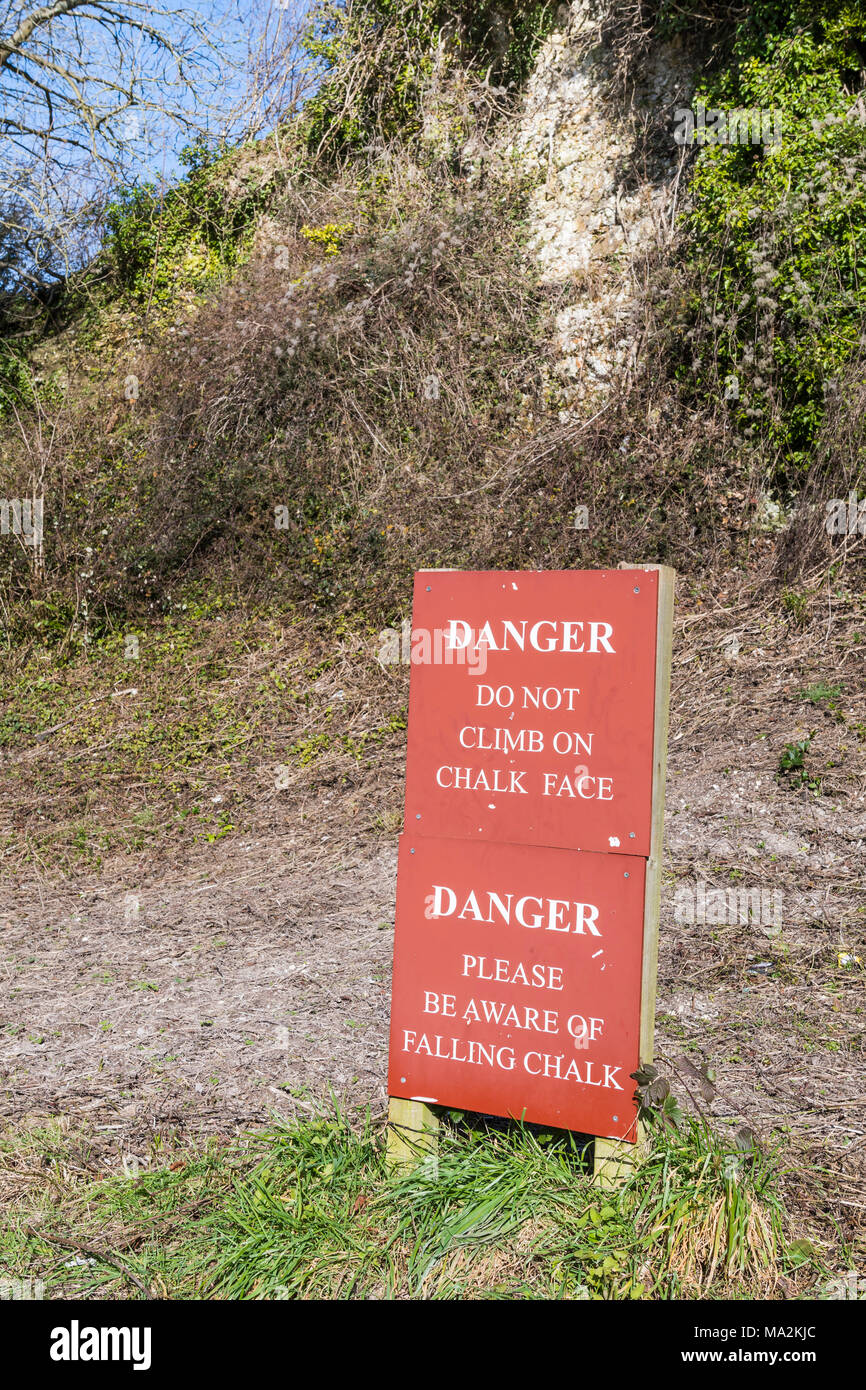 Danger, beware of falling chalk sign, by chalk rock face in the UK. - Stock Image