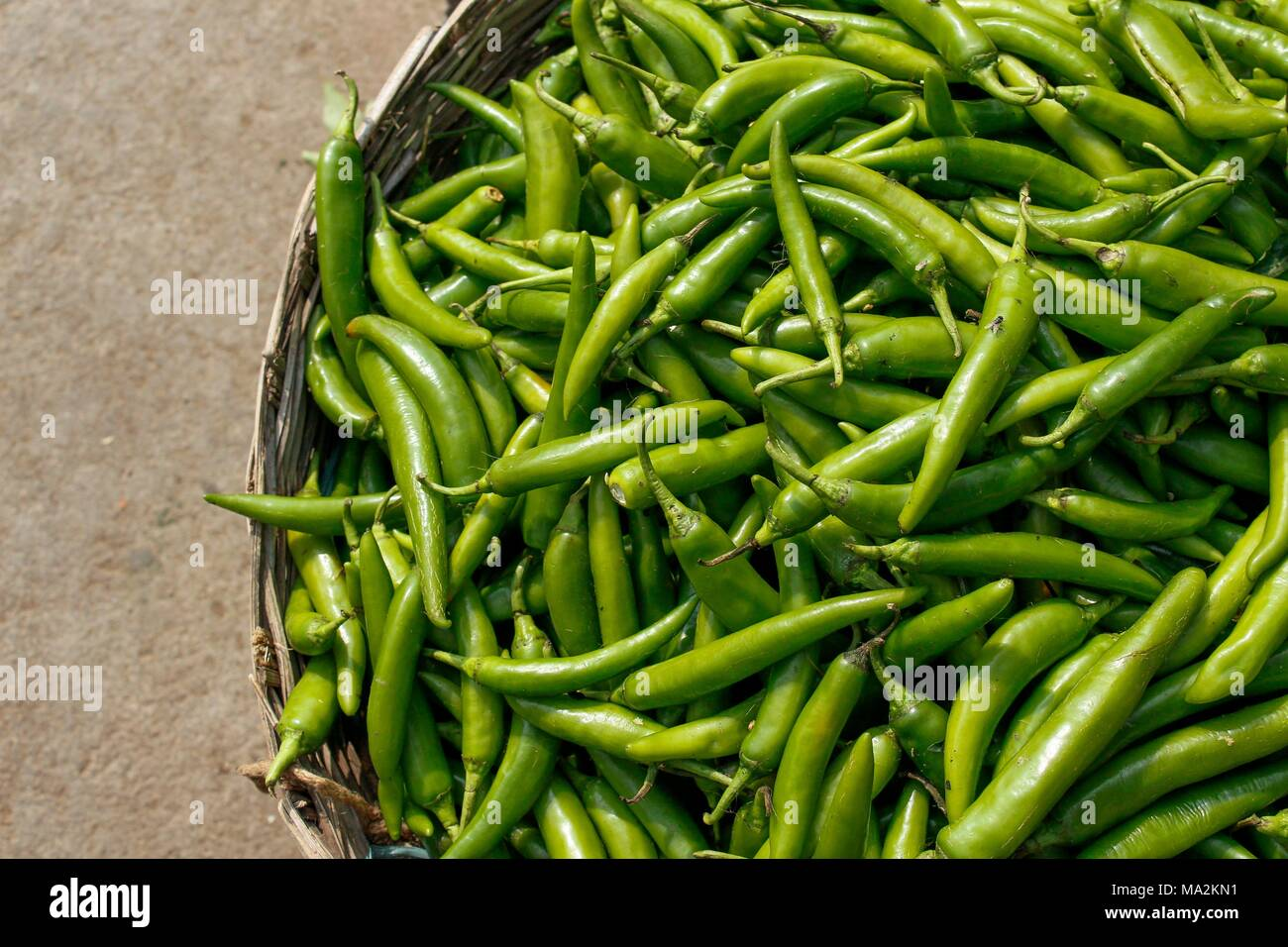 A basket of fresh green chillies on Indian market - Stock Image