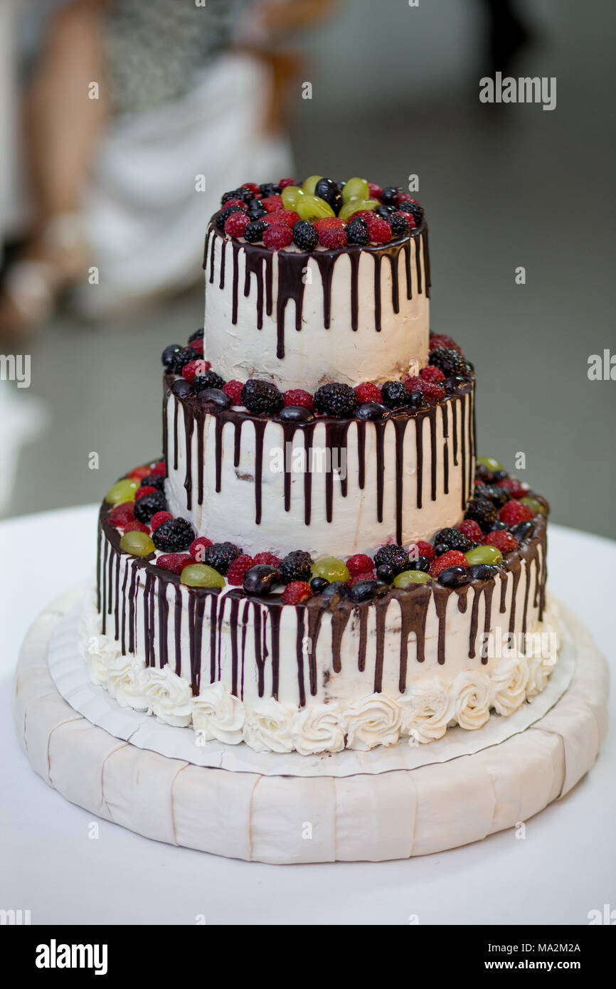 Three-tiered cake with berries - Stock Image