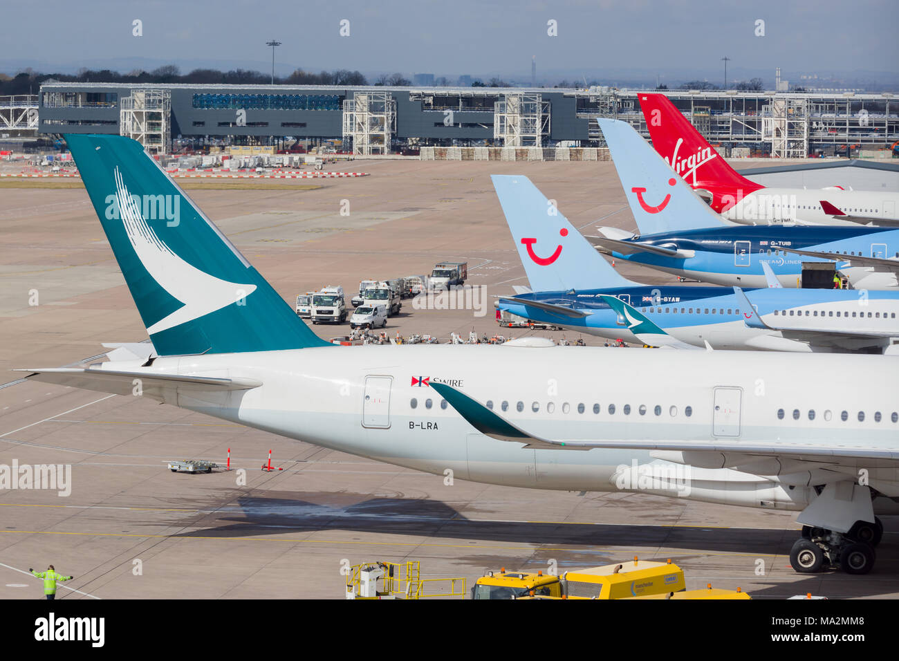 Various tail fins of airliners including Cathay Pacific, Tui and Virgin parked at terminal 2 in Manchester airport - Stock Image
