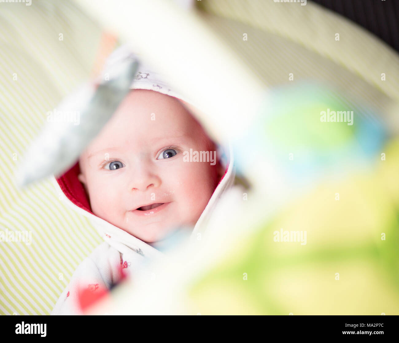 close up of very cute baby looking up through play activity baby gym