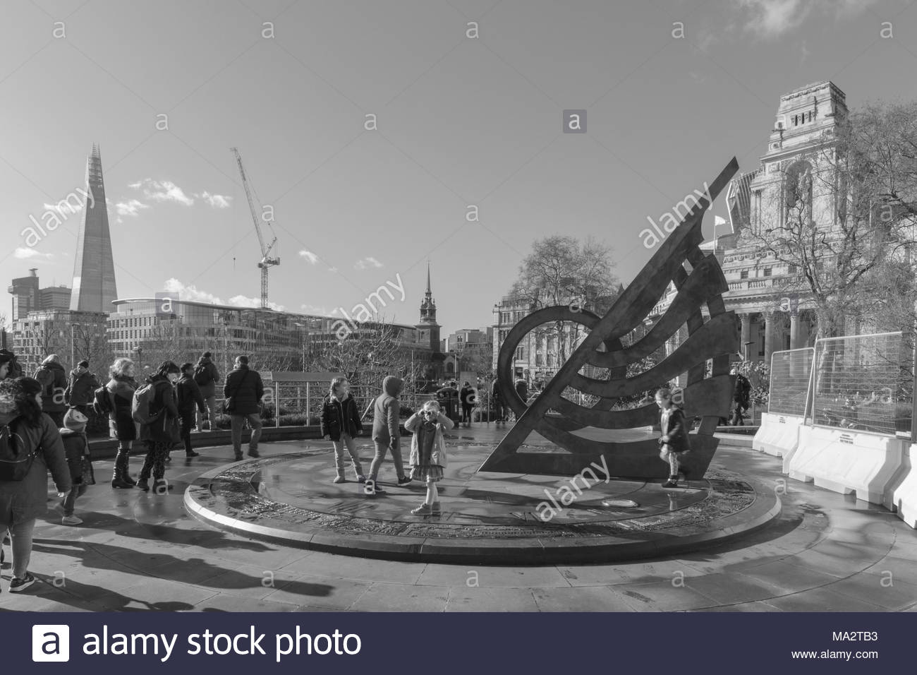 The bronze sundial above Tower Hill Underground Station. Sightseers are milling around the sundial some taking an interest in the history it depicts. - Stock Image