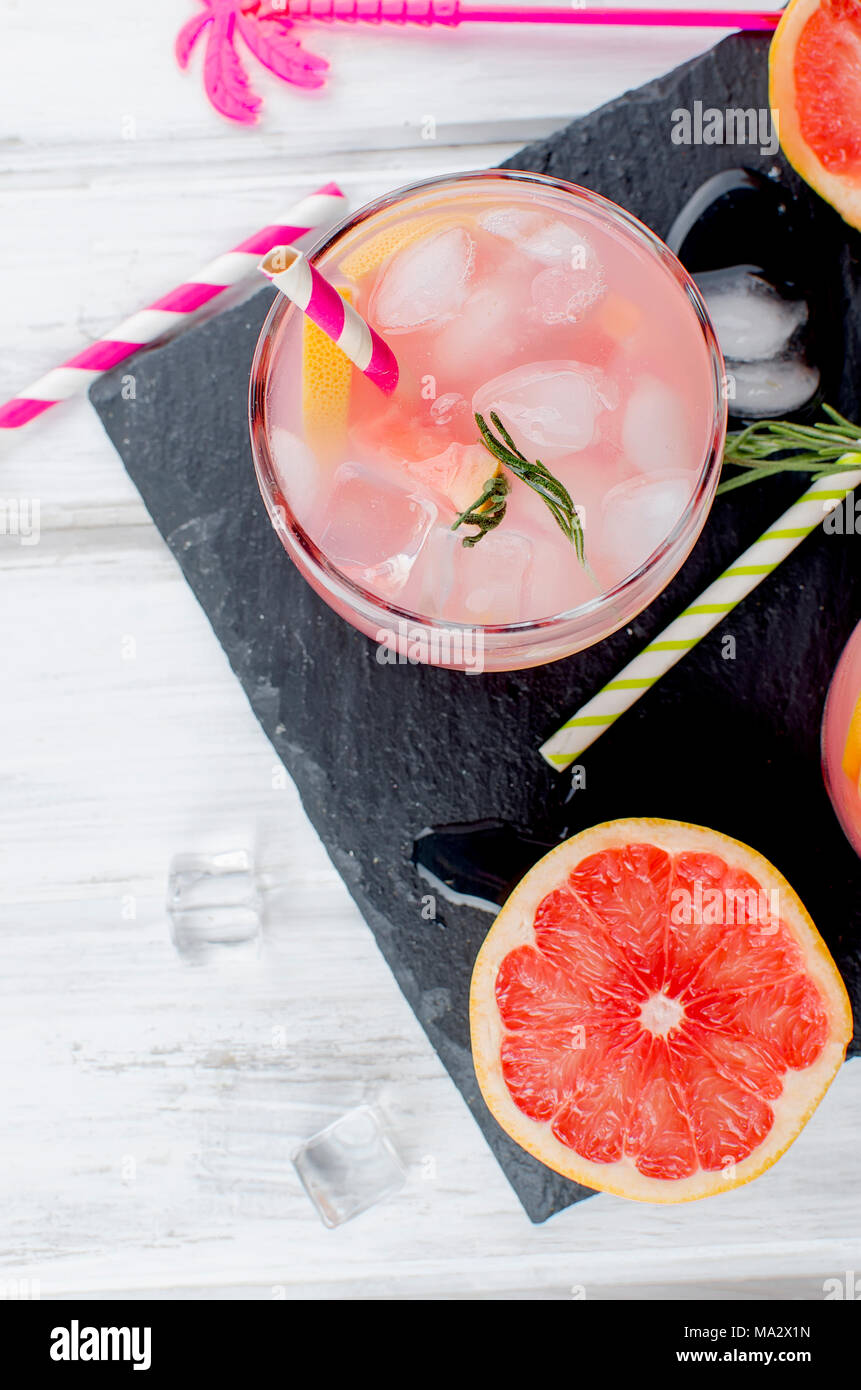 Cocktail with grapefruit slices and ice, ingredients for a drink on white wooden table, copy space - Stock Image