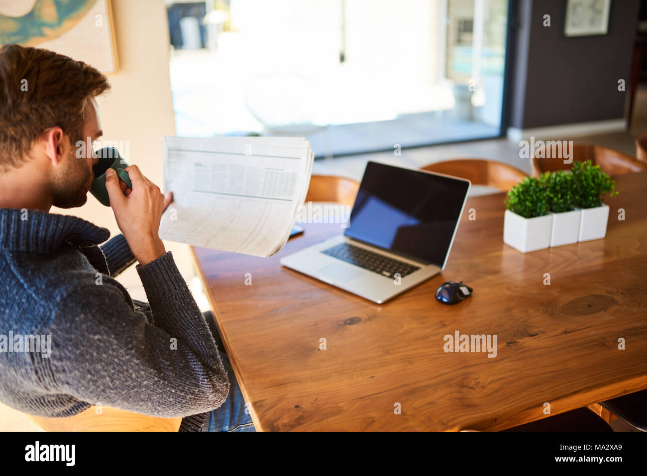 Caucasian man taking a sip of his morning cup of coffee while reading newspaper at his beautiful dining table, with his notebook in front of him for w - Stock Image
