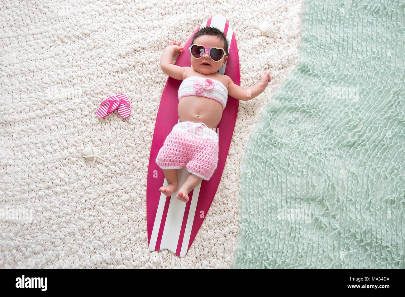 One month old baby girl lying on a tiny, pink and white surfboard. She is wearing sunglasses and a pink bathing suit. - Stock Image