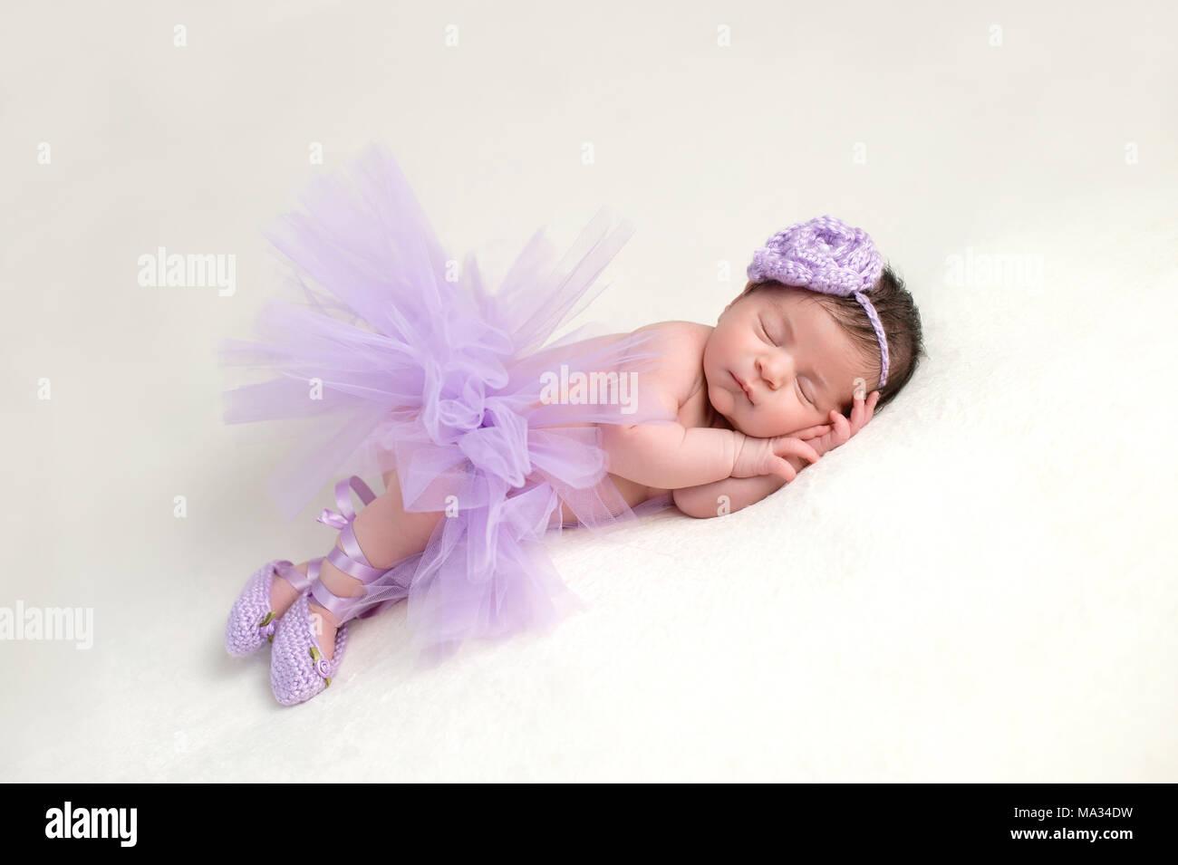 3c7dc81c1 Sleeping, newborn baby girl wearing a lavender colored, crocheted, flower  headband, ballet