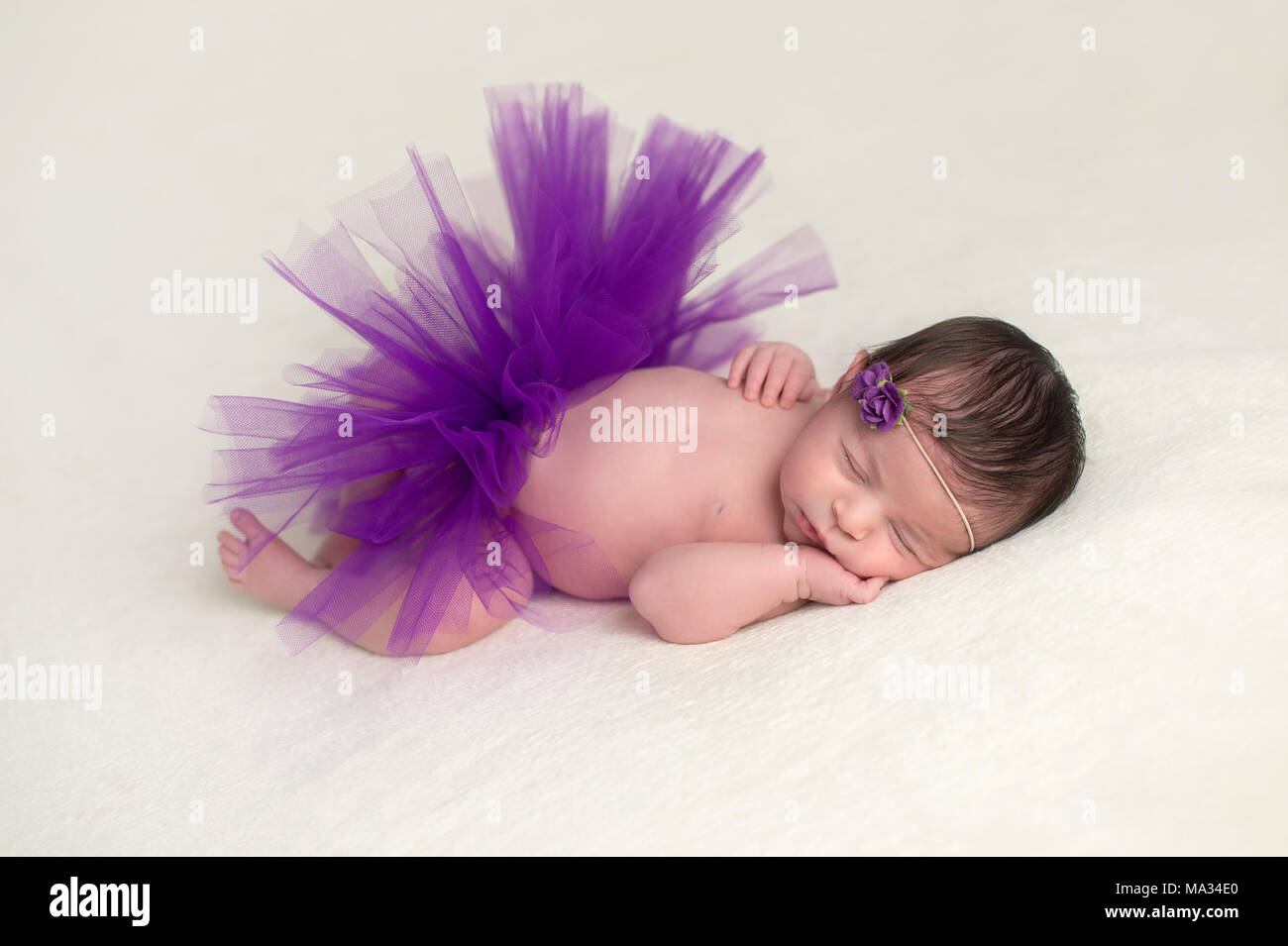 Sleeping Newborn Baby Girl Wearing A Purple Tulle Tutu And Flower