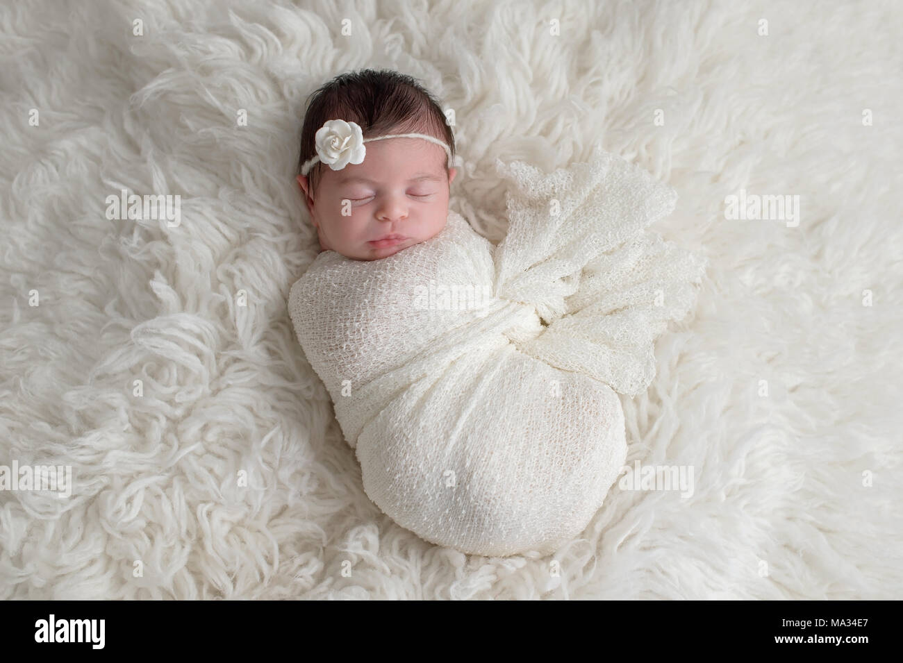 Sleeping Ten Day Old Newborn Baby Girl Swaddled In A White Wrap