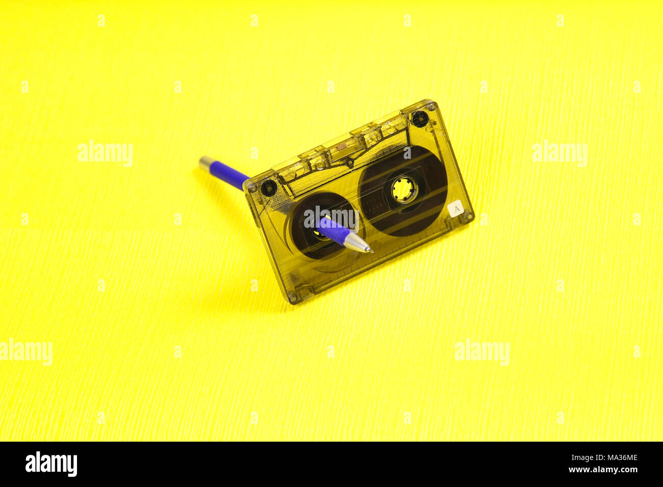Music of the past. Audio cassette with music of 80 years and a pencil for rewinding tapes of tape on a yellow background - Stock Image